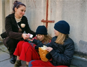 a woman giving money to street dweller kids, looking at them with pity